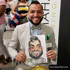 Men holding his funny cartoon at Austin trade show silly artist