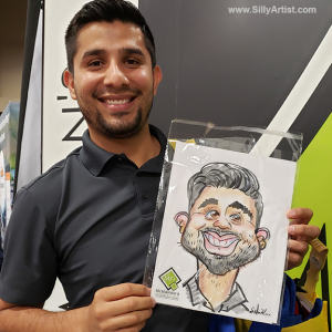 Man smiling holding his caricature at an austin trade show