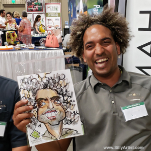man laughing at his caricature at Austin trade show silly artist